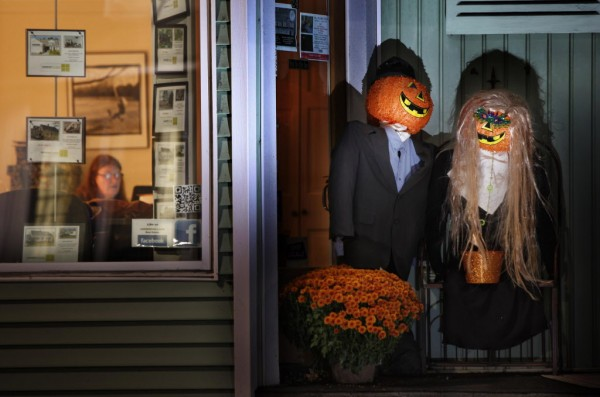 A Halloween couple stands in the doorway at Andrews Milligan Real Estate on Main Street in Kennebunk, where a woman works after hours on Monday evening.