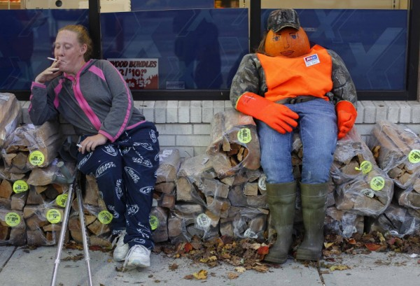 A woman shares a seat on a firewood pile with Patty Pumpkin at the XtraMart Kennebunk.