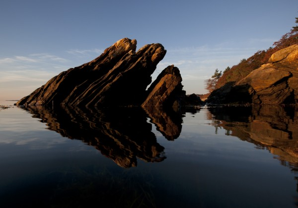 Rocks reflect in the still water at sunrise at Wolfe's Neck Woods State Park in Freeport.