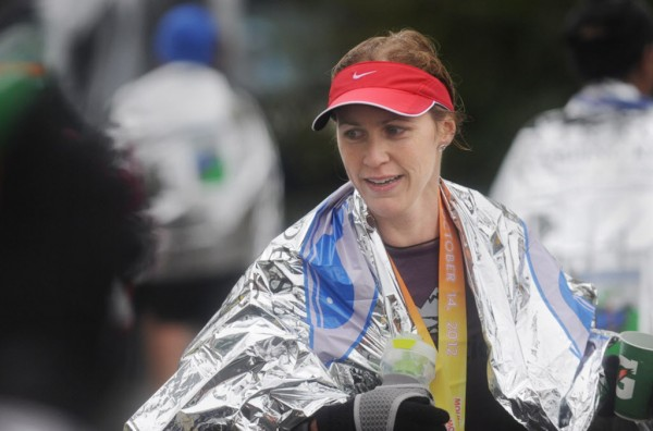 Leslie Peckwith of North Conway, N.H., wears a race-issued mylar blanket in the cold drizzle as she exits the finish area after taking second place in the women's division of the Mount Desert Island Marathon on Sunday, Oct. 14, 2012.