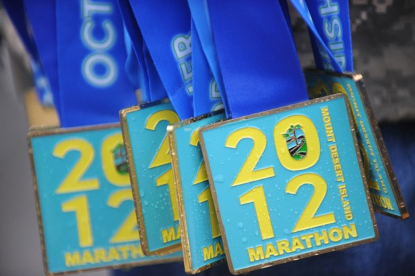 Medals, too many to count, await presentation at the finish of the Mount Desert Island Marathon on Sunday, Oct. 14, 2012.