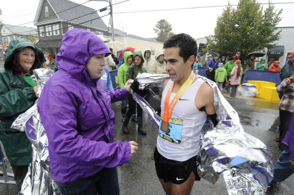 Mary Ropp, event coordinator and director for marketing for the Mount Desert Island Marathon, helps wrap a foil blanket around first-place men's finisher Louie Luchini on Sunday morning, Oct. 14, 2012.