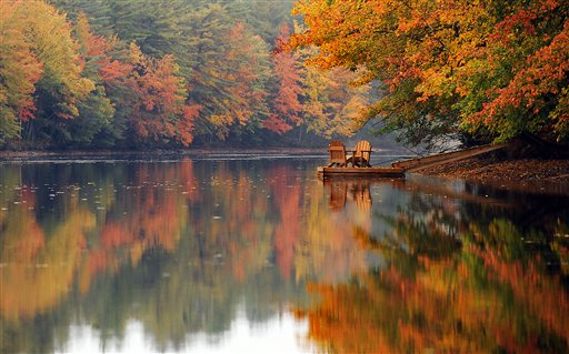 Two Adirondack chairs sit vacant on a dock along the misty shore of the Androscoggin River in Turner, Maine, Wednesday, Oct. 3, 2012, as the fall foliage nears peak color.