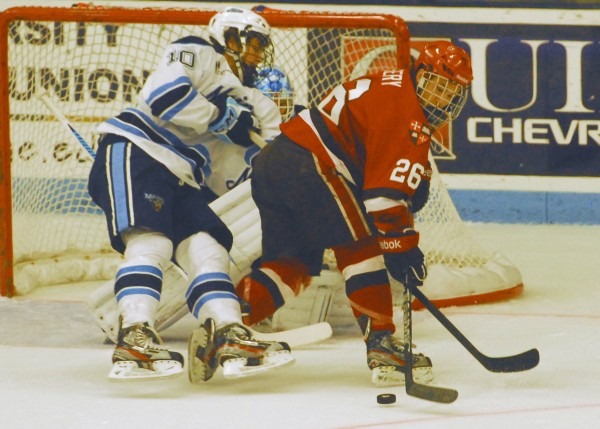 Maine's Ben Hutton (10) leaves the ice as he battles with St. Lawrence Kyle Essery (26) in front of the Maine goal during second-period action at Alfond Arena Saturday, Oct. 20 2012.