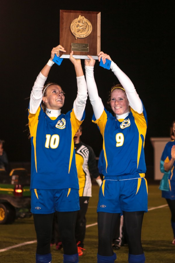 Hermon's Gabby Bryant (left)and Jessica Allen raise the championship trophy after beating Presque Isle 1-0 in overtime in the Eastern Maine Class B soccer final in Presque Isle Wednesday, Oct. 31, 2012.