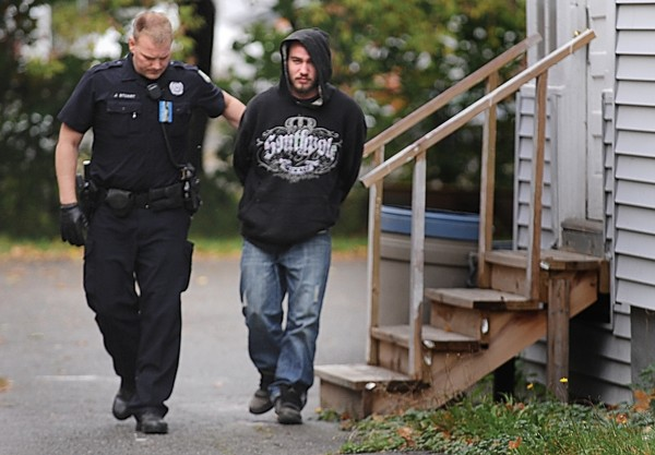 Bangor police officer Jason Stuart takes Kirk DePhilippo into custody around noontime Monday, Oct. 15, 2012, for his alleged role in a pharmacy robbery in Bangor.