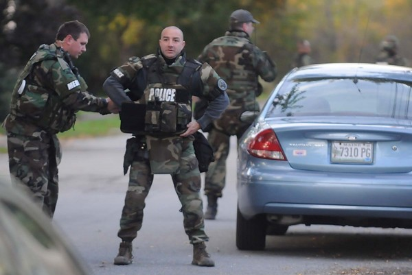 Members of Bangor police department's tactical unit gear up as they assemble to stake out a residence off Webster St. North Monday evening, Oct. 8 ,2012.