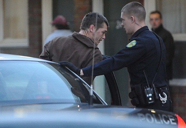 A Bangor police officer helps John D. Harmon, 27, of Dover-Foxcroft into the back of a patrol car during Monday evening's police action at Bangor Efficiency Apartments off Hammond St. Harmon was charged with Class B felony robbery.