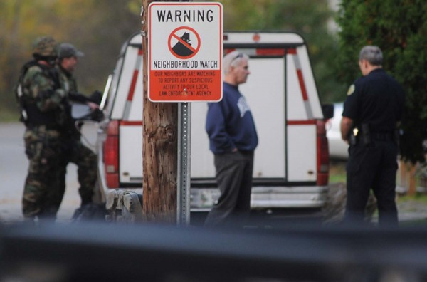 A neighborhood watch sign is posted near an area where members of Bangor police department's tactical unit gathered to stake out a residence off Webster St. North Monday evening, Oct. 8 ,2012.