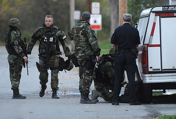 Members of Bangor police department's tactical unit assemble to stake out a residence off Webster St. North Monday evening, Oct. 8 ,2012.