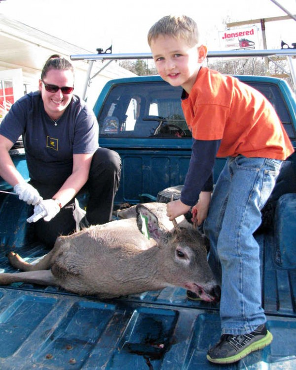 At the J&K Sporting Goods game-tagging station in West Paris, 5-year-old Collin Cole of Greenwood hefts a 4-point, 120- to 125-pound deer that his father, Matt Cole of Greenwood, shot Saturday in Greenwood on the opening day of Maine's regular firearms deer season. In back, Sara Robinson, an epidemiologist with the Maine Center for Disease Control and Prevention in Augusta, readies to take a sample of blood from the buck for testing for eastern equine encephalitis.