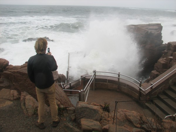 Logan Kline, a seasonal employee at Seawall Campground in Acadia National Park, uses his phone to take photos at Thunder Hole on Tuesday morning, Oct. 30, 2012.