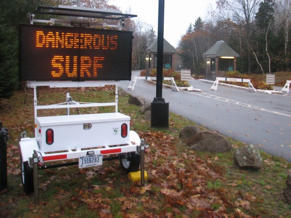 A sign at the Acadia National Park entrance station on Park Loop Road warns visitors Tuesday morning about large, hurricane-generated waves along the shore by Ocean Drive.