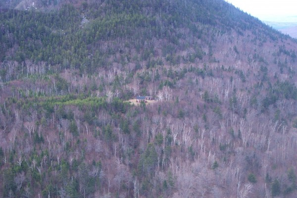 The old fire lookout cabin and woodshed is located in a clearing halfway up the trail to the summit of Big Spencer Mountain near Kokadjo, Maine, during the summer of 2004.