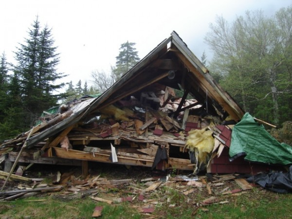 The old fire lookout's cabin on Big Spencer Mountain is torn down and ready to be burned in May 2012, a decision made by the Maine Division of Parks and Public Lands to ensure the safety of hikers and allow nature to reclaim the small clearing, which became a small piece of an ecological reserve when the state purchased the land in 2002.