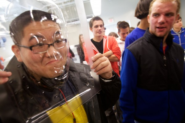 Mt. Ararat High School senior Andy Nguey jokingly tries on a mask made by simple vacuum thermo-forming at the Southern Maine Community College composites lab on the Brunswick campus Wednesday, Oct. 17, 2012, during its first STEM conference.