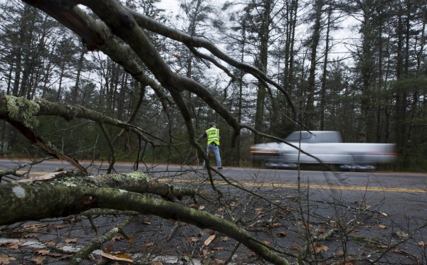 A firefighter directs traffic around a downed tree during the the early stages of Hurricane Sandy, Monday, Oct. 29, 2012, in Old Orchard Beach, Maine. Hurricane Sandy continued on its path Monday, as the storm forced the shutdown of mass transit, schools and financial markets, sending coastal residents fleeing, and threatening a dangerous mix of high winds and soaking rain.