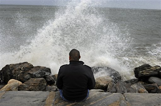 Lamar Chambers watches waves as winds from hurricane Sandy reach Seaside Park in Bridgeport, Conn., on Monday, Oct. 29, 2012. Hurricane Sandy continued on its path Monday, forcing the shutdown of mass transit, schools and financial markets, sending coastal residents fleeing, and threatening a dangerous mix of high winds and soaking rain.