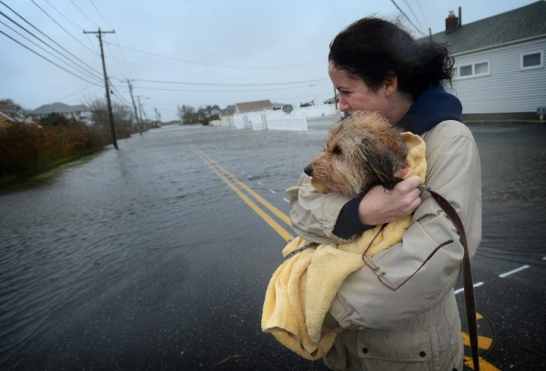 Heather Moline, of Oakdale, wraps her dog Tokio in a towel as she comes out in the rain to survey the flooding on Browns River Road in Sayville, on Long Island's South Shore, Monday afternoon, October 29, 2012, as Hurricane Sandy gains strength.
