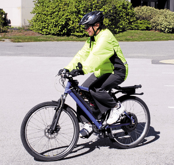 "Victoria Blanchette rides her ebike across the University of Maine campus last week. Blanchette makes a daily 20-mile roundtrip commute from Bangor to Orono; she researched the ebike before building it to determine if the bike could save on gas and also provide a ""greener"" commute."