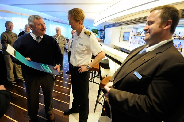 Joined by other Eastport leaders during their onboard reception and tour, Eastport City Council President Bob Peacock, left, presents the vessel's Captain Erik Bredhe, center, with artwork from the city. On the far right is Otto van der Westhuizen, the vessel's front office manager.