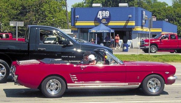 A 1970 Mustang rolls along Woodward Avenue in Detroit during the annual Wodoward Dream Cruise, which highlights American-made cars and Detroit, the city long associated with the American automotive industry.
