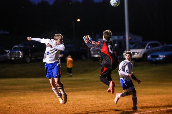 Central Aroostook's Joe Stiles heads the ball wide as Southern Aroostook goalkeeper Austin White comes out to challenge during their game Thursday night in Mars Hill. Central Aroostook's Dustin Pryor watches the play. Southern Aroostook won 2-1.