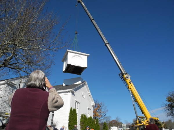 A woman watches Wednesday morning as the clock tower segment of the Community Church of Stockton Springs' new steeple is hoisted into position. Steeplewright Robert Hanscom of Greene is crafting a replacement for the 1860 steeple that had to be taken down in 2008.