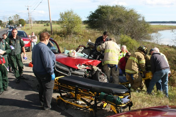 Emergency crews try to free Eli Ranquist from his wrecked car on the River Road in Cushing on Monday afternoon.