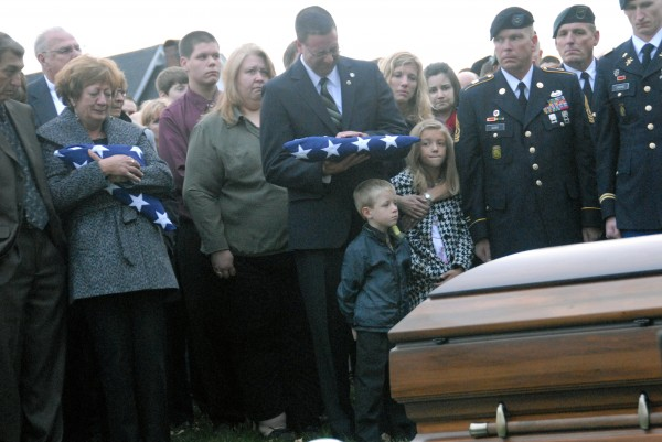 Sam Henderson cradles a second American flag given to him by a U.S. Army honor guard during the funeral of his brother, Sgt. 1st Class Aaron Henderson, in the East Hodgdon Cemetery on Wednesday, Oct. 10, 2012. The Hendersons' mother, Christine Henderson, holds the first.