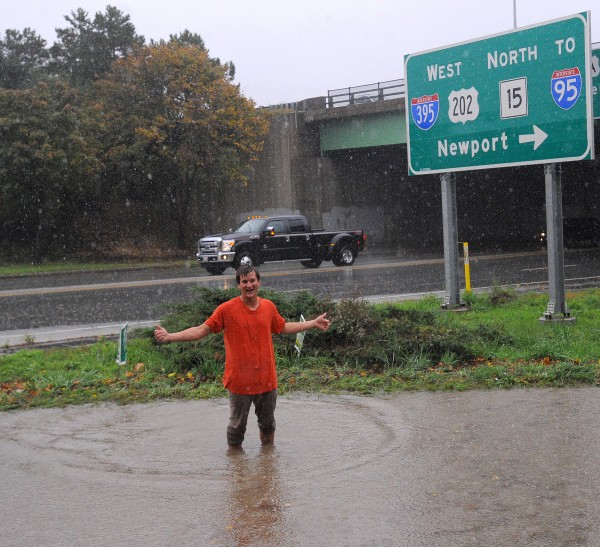 A motorist stands in the water on the I-395 onramp. He said that his car was one of at least two that were temporarily disabled in the high rain runoff.