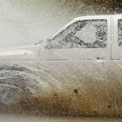 A car drives through floodwater on Broadway in Bangor after heavy rains caused flooding and washed out some roads in the region on Saturday, Oct. 20, 2012.