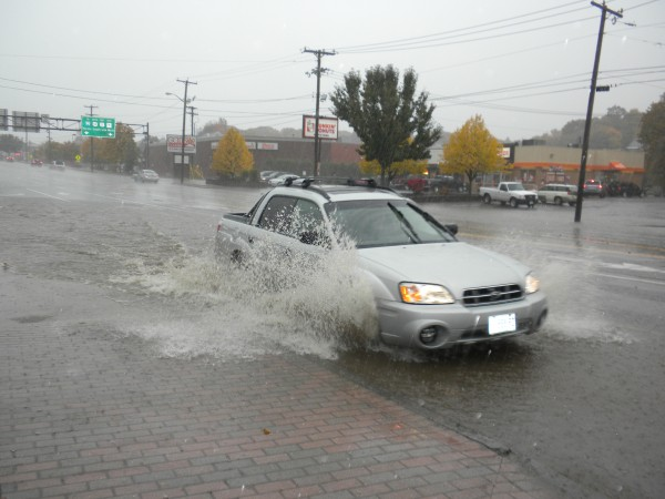 A Subaru takes a right onto Railroad Street and creates quite a splash with water flooding the street on Saturday, Oct. 20, 2012.