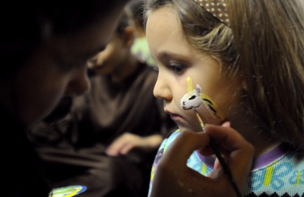 Three-year-old Chloe Oliver gets her face painted by Andrea Graichen during the 10th annual Pumpkins in the Park Community Halloween Party at the Bangor Auditorium on Saturday, Oct. 21, 2012.
