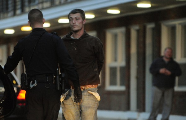 Bangor police take John D. Harmon, 27, of Dover-Foxcroft into custody in the parking lot of the Bangor Efficiency Apartments after removing him from 27 Webster Ave. on Monday, October 8, 2012.