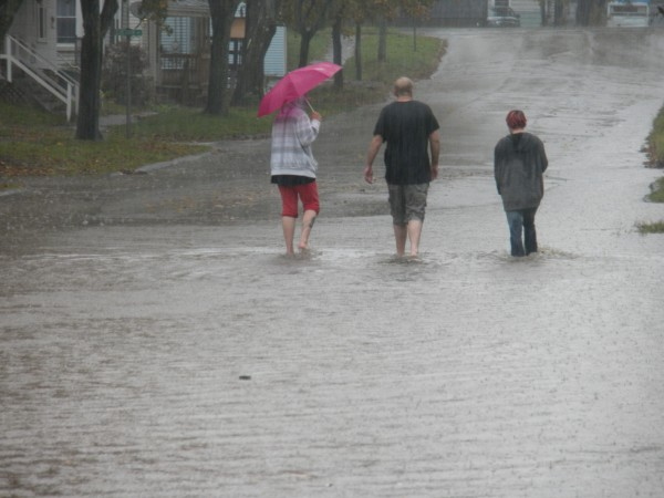 Nicole Smith (from left), Travis Smith and Jessie Wallace walk down Sanford Street, which flooded Saturday morning during a heavy downpour. &quotYou just missed me. I was out there swimming,&quot Travis Smith joked. The road flooded all over town, he said, because the fallen leaves have plugged the drains.