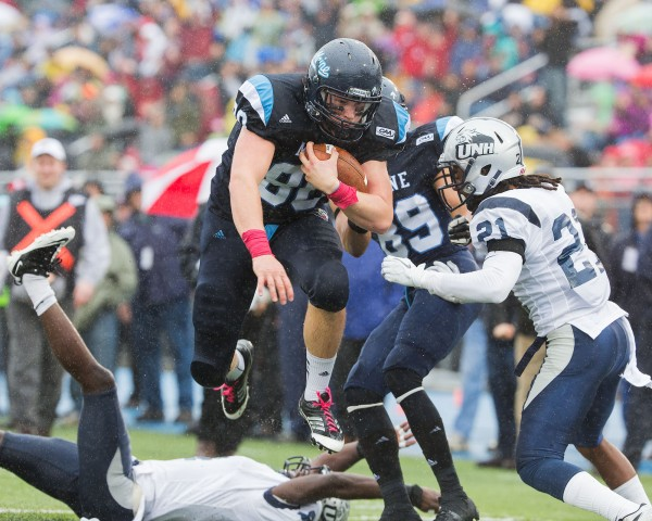 Justin Perillo (80) leaps a UNH defender to score a touchdown and put Maine up 14-7 in the second quarter. UNH's Steven Thames (21) is in the foreground.