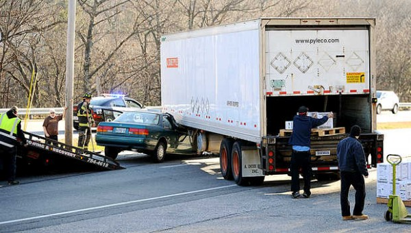 People unload a delivery after the tractor-trailer was involved in an accident on Monday afternoon on Washington Street in Auburn.