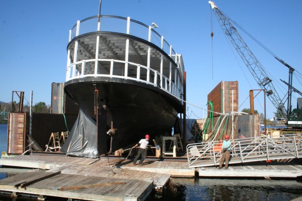 Workers float a platform in front of the keel of the 115-foot, 210-ton Katahdin cruise ship. The ship rests on floating barges, which were installed with pipes that can exchange air and water. The barges were taken out Moosehead Lake where they were sunk by pumping water into the pipes; the Katahdin then was maneuvered onto the barges. Once the ship was secured, the water in the pipes was replaced with air to float the barges. The barges, with ship, were returned to East Cove in Greenville, where repairs are now under way.