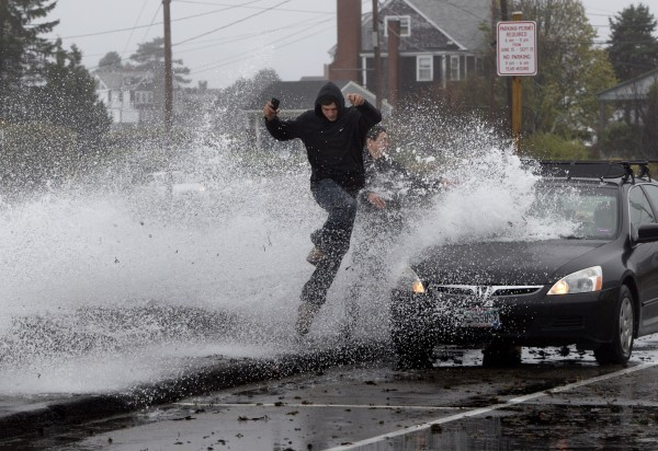 Caleb Lavoie, 17, of Dayton, Maine, front, and Curtis Huard, 16, of Arundel, Maine, leap out of the way as a large wave crashes over a seawall during the early stages of Hurricane Sandy in Kennebunk. A storm predicted for next week is expected to bring more rain and snow.