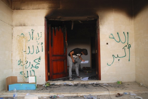 A man looks at documents at the U.S. consulate in Benghazi, Libya, days after an attack that killed four Americans, including Ambassador Chris Stevens. The graffiti reads, &quotno God but God,&quot  &quot God is great,&quot and &quotMuhammad is the Prophet.&quot CIA security officers went to the aid of State Department staff less than 25 minutes after they got the first call for help during the attack on the U.S. Consulate in Benghazi, Libya, U.S. intelligence officials said Thursday.