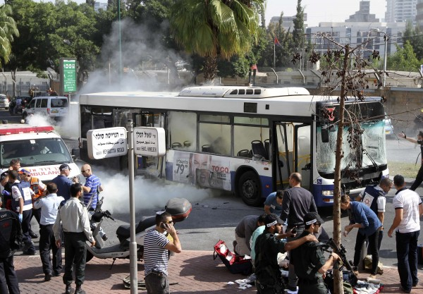 A wounded woman is treated on the ground as smoke rises from a bus after an explosion in Tel Aviv on Wednesday.