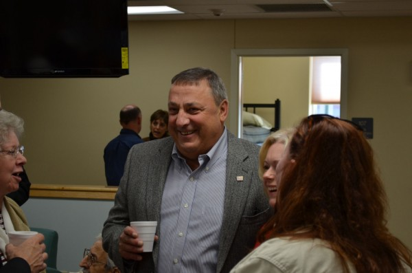 Gov. Paul LePage (center) talks with a group of people inside the new Mid Maine Homeless Shelter in Waterville in October 2012.