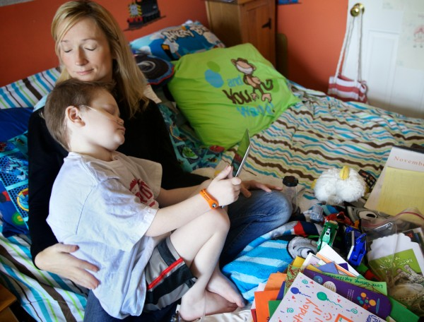 Kate St. Clair cuddles her son Kyle, 8, for a moment while he plays a game on his iPad Thursday, Nov. 1, 2012 at their home in Scarborough.