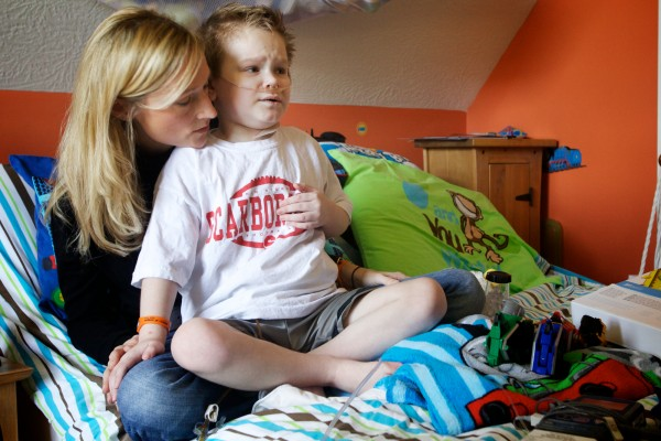 Kyle St. Clair, 8, grimaces, clutching his chest, as he is overtaken by pain in his mother, Kate's, lap Thursday, Nov. 1, 2012 in Scarborough. A second later his nurse Merydeth Charlton delivered a quick dose of painkillers through a line Kyle wears around the clock.
