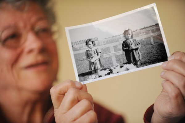 Paula Turcotte of Bangor holds up a photo of her two sisters, Tonny Moermans (left) and Mimi Moermans, taken around 1946, at the Margraten American Cemetery, several miles from their family's home in the Netherlands.