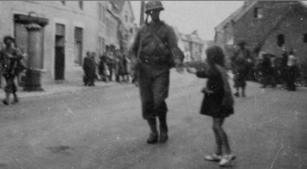 Paula Turcotte, then eight years old, is seen giving a U.S. soldier a cookie as the American forces came through her hometown on Sept. 13, 1944, during their effort to liberate Netherlands during World War II.