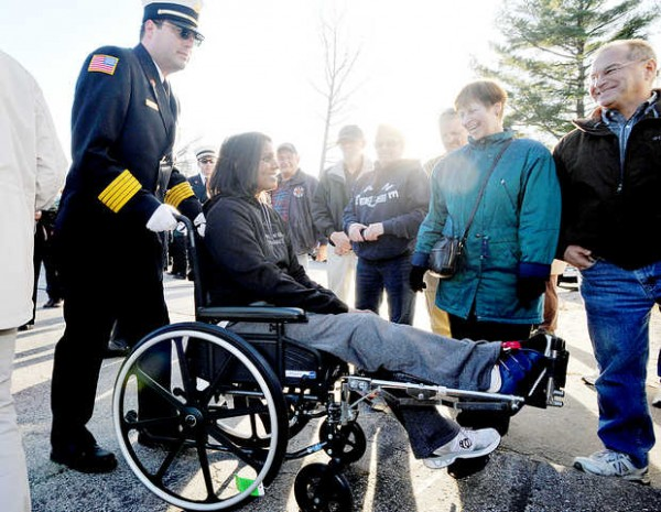 Livermore Falls Fire Chief Gerry Pineau pushes Army Sgt. Helaina Lake past a crowd of cheering people at the Knights of Columbus in Jay on Tuesday.