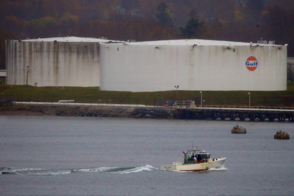 A lobster boat passes oil tanks on the South Portland side of Portland Harbor Tuesday Nov. 13, 2012.