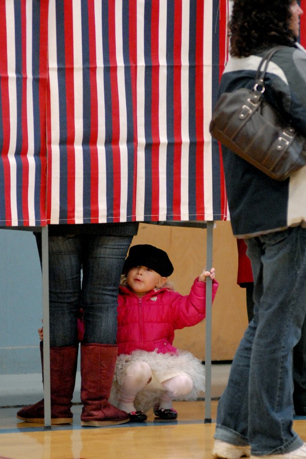 Eden Walton, 3, watches voters file by her booth with their ballots as she waits for her mom Melissa Walton to vote Tuesday morning at the Brewer Auditorium.